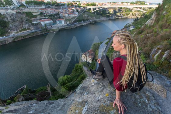 Young woman with backpack sitting on cliff's edge and...
