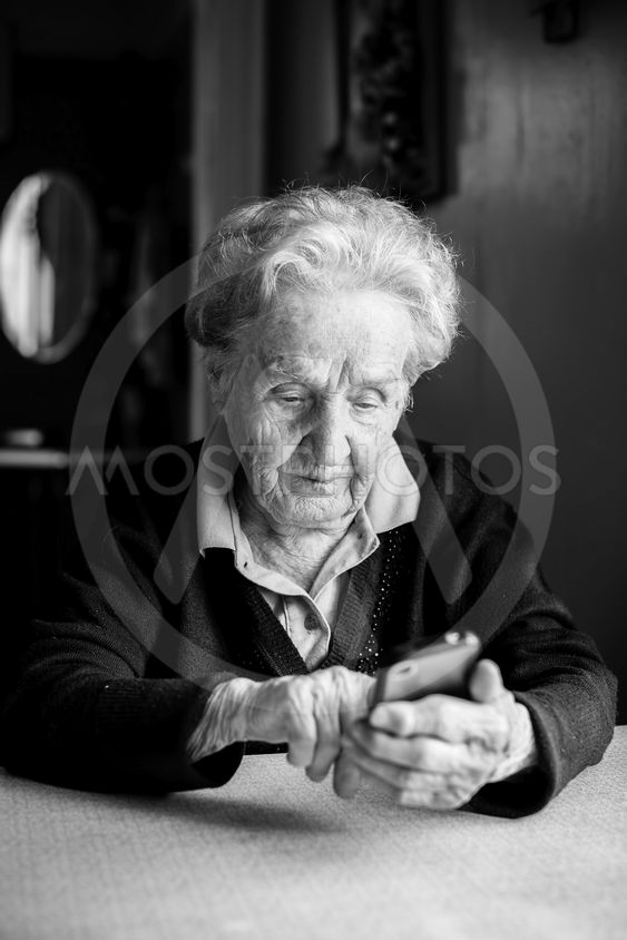 Old woman takes on smartphone sitting at the table in the...