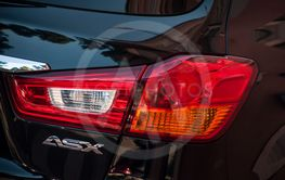 rear light and sign on black Mitsubishi crossover parked...