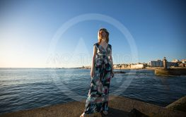 Woman in a long dress standing on the seafront.