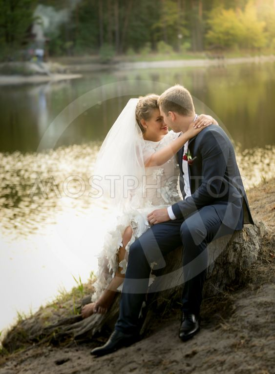 just married couple hugging on the riverbank