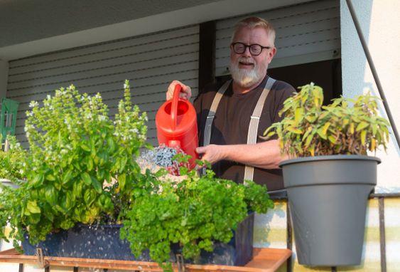 Smiling Senior watering herbs