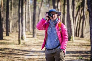 tourist woman in the forest with photo camera