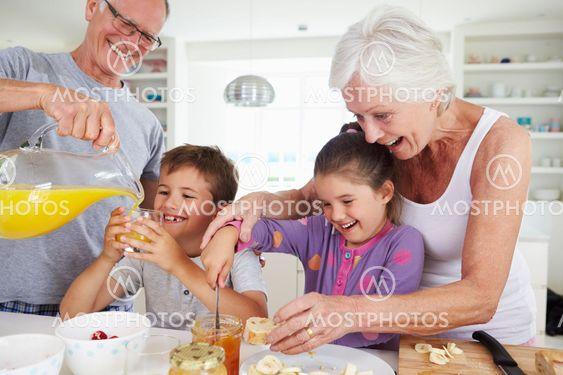 Grandparents With Grandchildren Making Breakfast In Kitchen