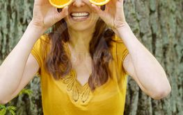 Laughing young woman with orange eyes