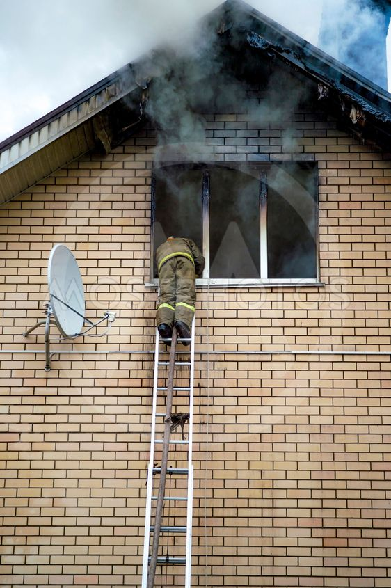 A firefighter puts out a burning building with height...