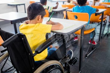 A pupil in wheel chair working at his desk