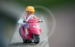 Playmobil figurine on red scooter in outdoor