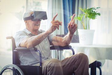 Happy senior man on wheelchair using VR headset