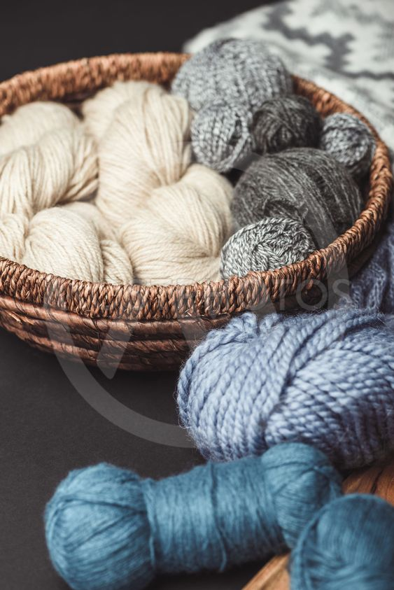 close up view of knitting clews in wicker basket on dark...