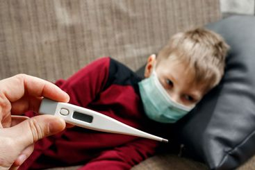 A father in the hands with a fever thermometer for a boy...