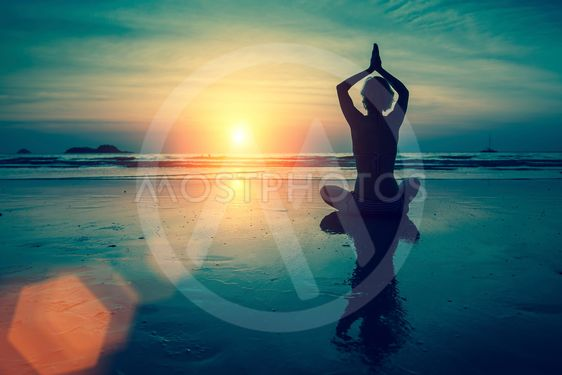 Silhouette of woman practicing yoga in Lotus position at...
