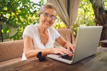 Happy senior woman use wireless headphones working...