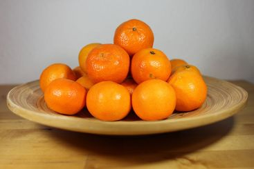 Stacked tangerines on a wooden plate on a wooden table...