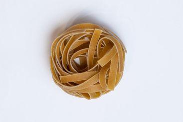 Raw whole grain brown pasta Tagliatelle