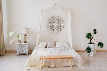 Bedroom with four-poster bed, bedside tables and flowers.
