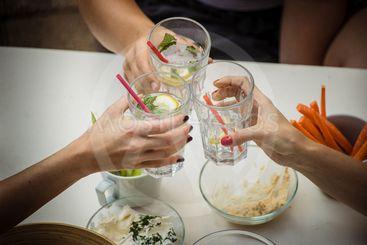 Three women cheering with gin tonic
