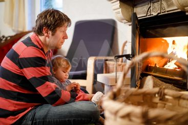 Middle age father sitting by fireplace with cute little...