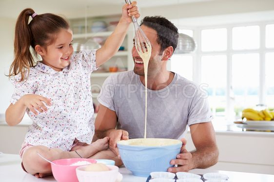 Father And Daughter Baking Cake In Kitchen