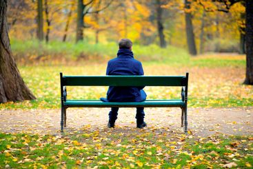 Lonely man sitting on a wooden bench in autumn day