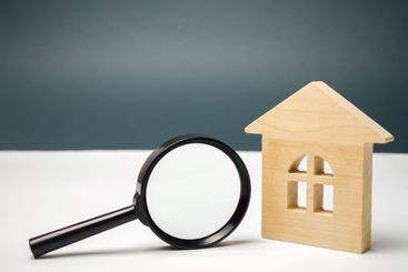 Wooden house and magnifying glass. Property valuation....