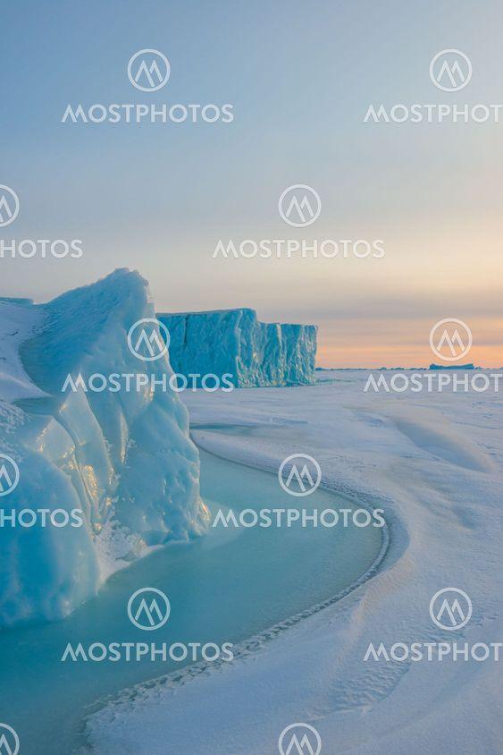 Ice berg on frozen sea at sunrise