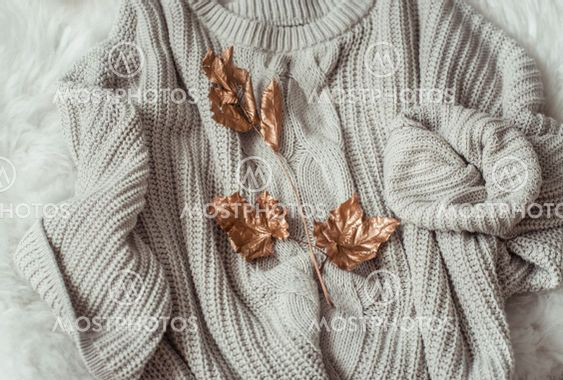 Autumn background with cozy sweaters and gold leaves .