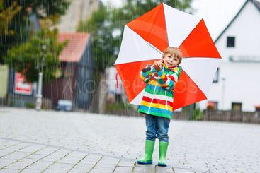 Smiling boy with yellow umbrella and colorful jacket...