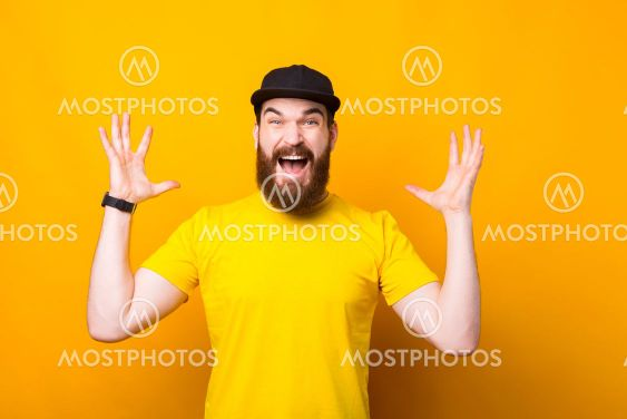 Portrait of young bearded hipster man making surprised...