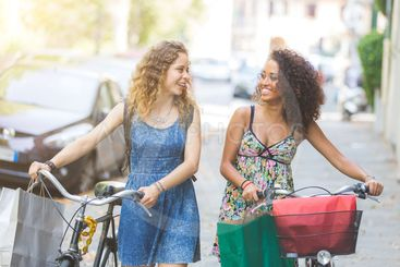 Multiracial couple of friends with bikes.