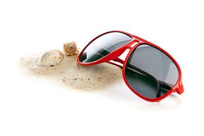 Sunglasses, sand and shells