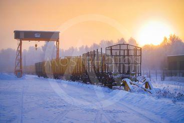 Lastkran och godsvagnar i solnedgång i ett kallt...