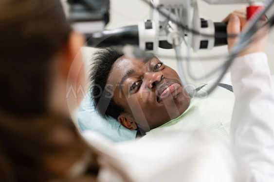 Young African American male patient at chair at dental...