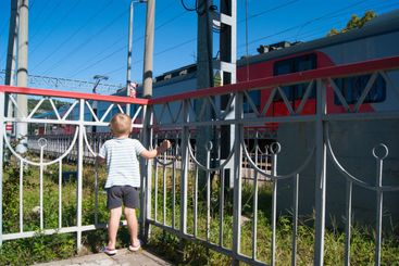 A little blond-haired boy of three years old stands near...