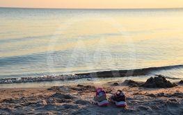 Skor står på badstranden i solnedgången