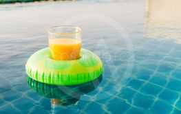 Orange juice glass with swim ring at outdoor swimming pool