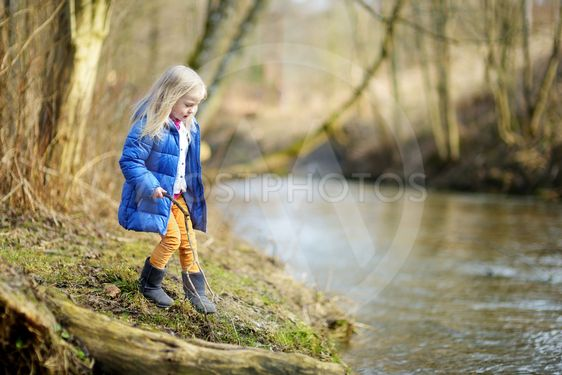 Adorable girl playing with a stick by a river