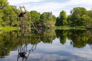 Artwork with rusty pipes forming two chairs in a pond.