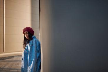 Sad woman hiding in shadows on urban background