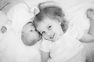 big sister lying next to a newborn baby.