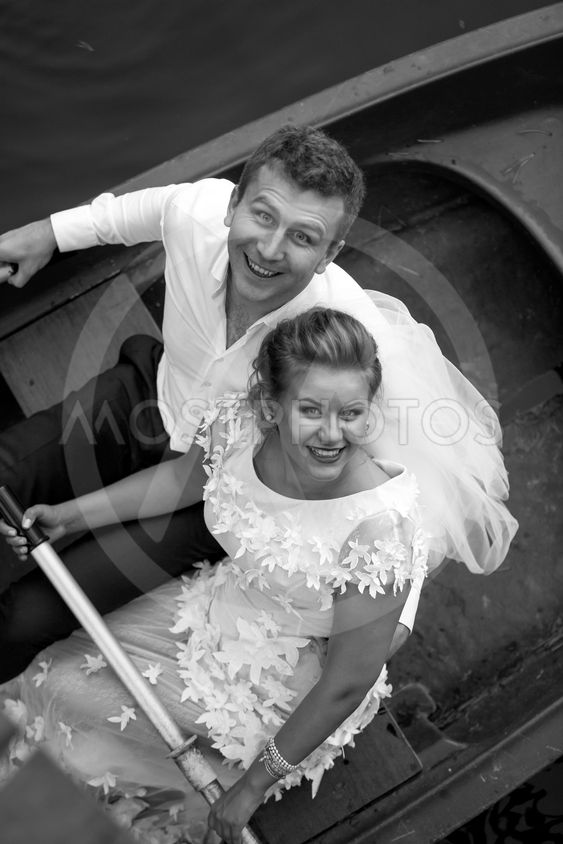 Portrait of smiling bride and groom sitting on rowing boat