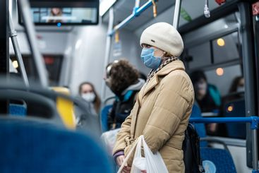 A woman in abus with a medical mask on her face.