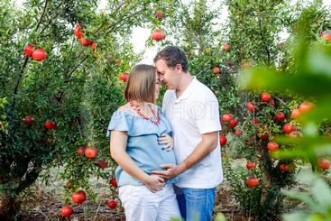 Portrait of happy family in the pomegrate fruit garden....