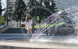 Teen near a splashing fontain in the center of town 12...