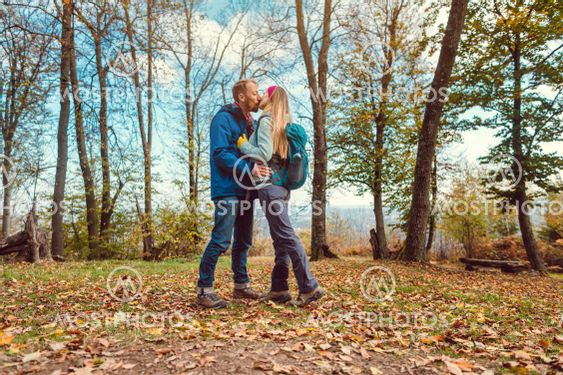 Couple of man and woman kissing during walk in fall