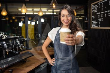 Smiling barista holding disposable cup