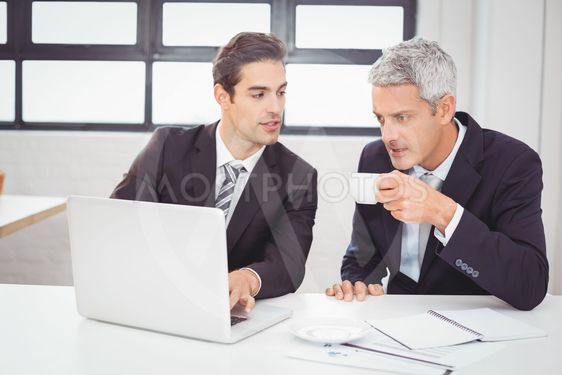 Businessman having coffee while working with colleague