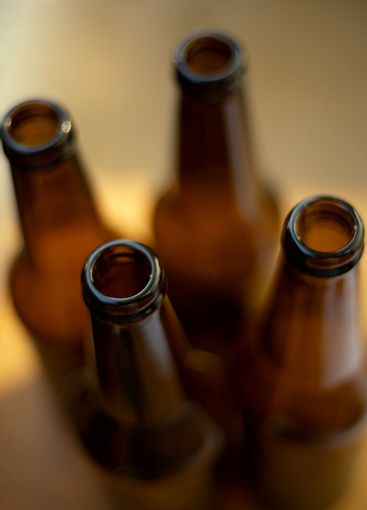 Four dark empty beer bottles on the table