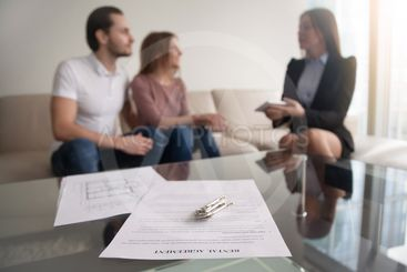 Couple meeting with realtor, focus on rental agreement...