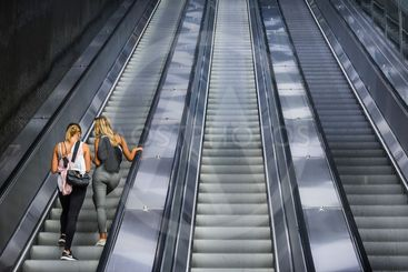 Two women standing in one of three escalators at railway...